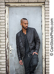 Attractive young black man standing in door way - Portrait...