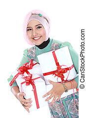 Happy young muslim woman with gift boxes isolated over white...