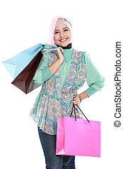 Beautiful young muslim woman holding a few shopping bags -...