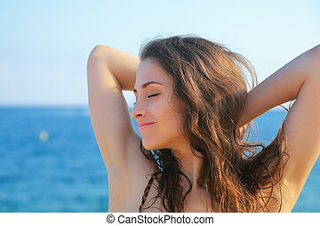 Beautiful woman relaxing with closed eyes on blue sea...