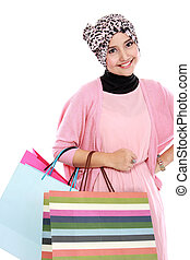 Happy young muslim woman with shopping bag isolated over...