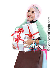 Happy young muslim woman with shopping bag and gift boxes...