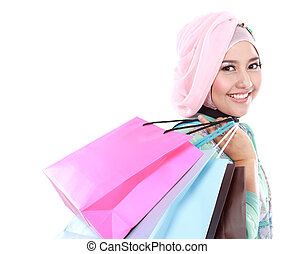 Beautiful young muslim woman holding a few shopping bags -...