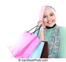 Closed up of happy young muslim woman with shopping bag...