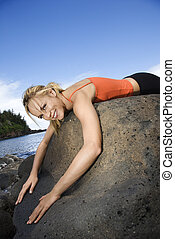 Woman draped over large rock. - Caucasian young adult woman...