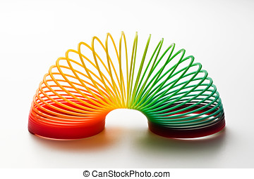 Rainbow coloured slinky toy made of a plastic wire spiral...