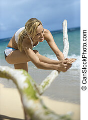 Woman stretching on beach - Caucasian young adult woman...