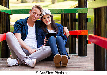 loving teen couple with tablet computer outdoors
