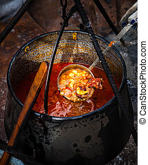 Traditional Goulash soup in cauldron - Traditional...