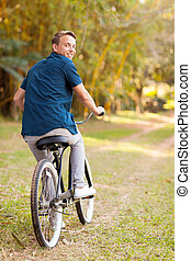 joyful teen boy riding a bicycle