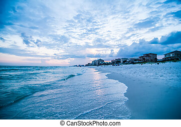 sunset on florida beach with white sand and blue sky
