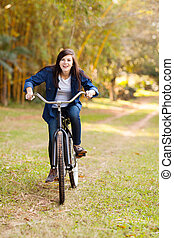 cute teenage girl riding a bicycle outdoors in the park