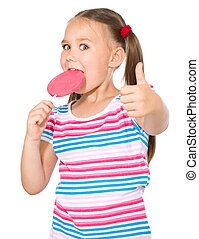 Little girl with lollipop showing thumb up gesture