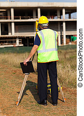 rear view of land surveyor working at construction site -...