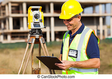 mid age land surveyor working at construction site with...
