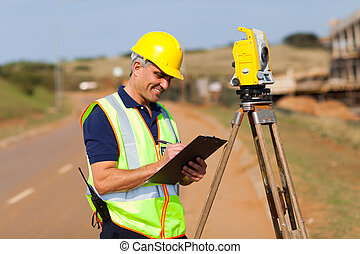 land surveyor - senior surveyor working on the road
