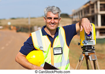 middle aged land surveyor outdoors - middle aged land...