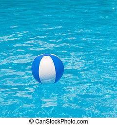 White and blue beach ball floating on a sparkling blue swimming pool
