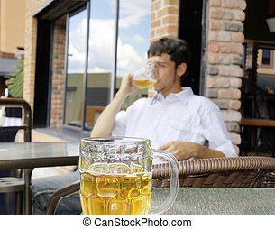 Young man drinking beer, focus on front glass bock