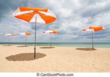 Beach umbrellas on sand beach. Concept for rest, relaxation,...