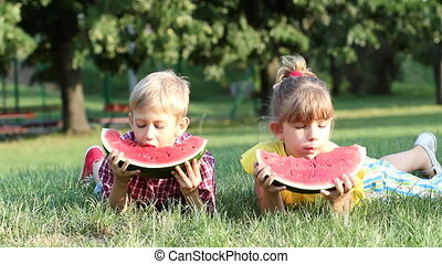 boy and little girl eat watermelon