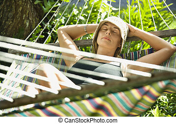 Woman relaxing in hammock - Caucasian mid-adult woman...