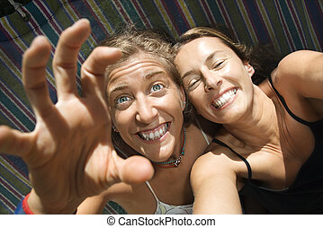 Women being silly in hammock.