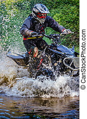 Quad rider through water stream in the forest.