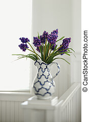 Purple flowers in pitcher vase.