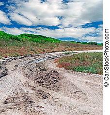 clouds and dirt road - dirt road under a cloudy sky in...