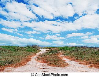dirt road and clouds - dirt road under a cloudy sky in...