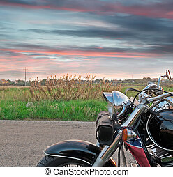 Motorcycle at sunset - chromed motorcycle on the edge of the...