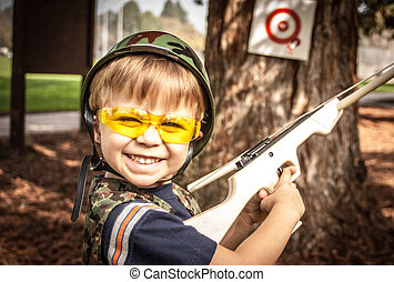 Boy Playing with Toy Crossbow Gun - Young boy target...