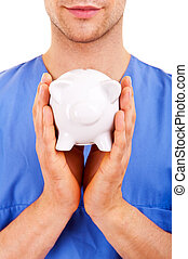 Doctor with Caring Hands on a Piggy Bank.