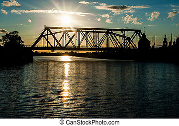 the railway bridge through the river at sunset - silhouette...