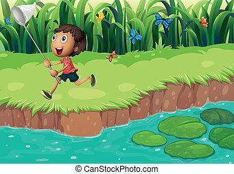 A boy catching butterflies at the riverside