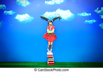 funny ponytails - Happy little girl with a book in hand is...