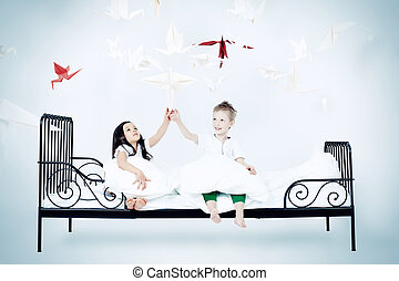 catch a dream - Cute kids sitting together on the bed under...