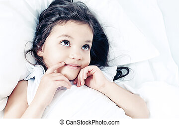 cozy bed - Sweet little girl is going to sleep in a bed