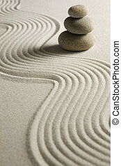 Stack of stones on raked sand; zen concept