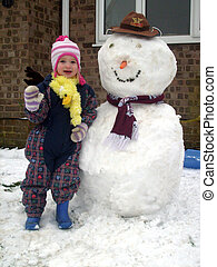 Cute child and snowman - Cute child waving as she stands...