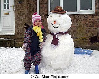 Baby stood next to snowman - Close up of young baby stood...