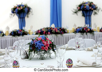 Laid table at wedding reception, focus on bouquet on table.