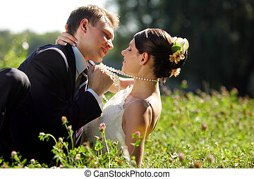 Newlywed couple romancing in field