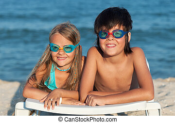 Kids with swimming goggles on the beach having fun
