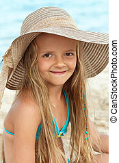 Little girl on the beach portrait smiling with a large hat