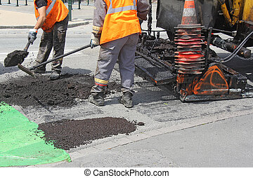 Paving roads - Workers on Asphalting paver machine during...