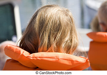 lifevest - little girl wearing an orange lifevest