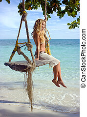 Girl on swings - Girl sitting on rope swings on the beach