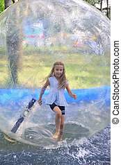 Zorbing The girl runs inside a transparent sphere